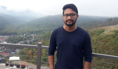 Graduate student Mominur Rahman standing against a backdrop of a foggy mountain