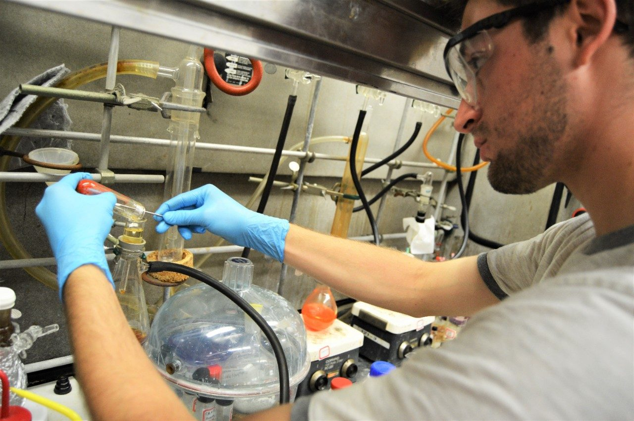 Inorganic Graduate Student working in a fume hood wearing gloves and safety glasses